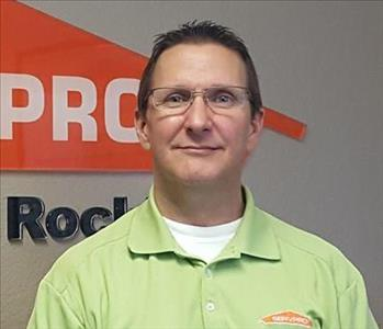 Male employee wearing a green SERVPRO shirt standing in front of a SERVPRO sign