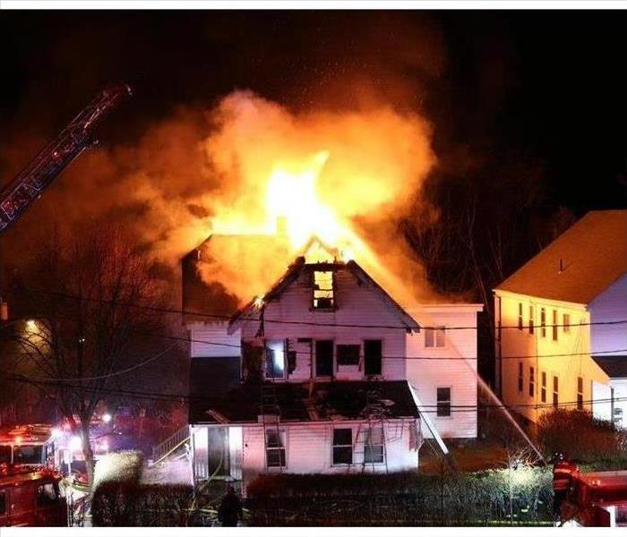 Home with roof engulfed in flames